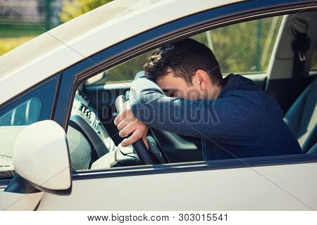 Nearly Sleeping Casual Man Keeps Hand And Head On The Steering Wheel Being Tired Waiting In The Traf