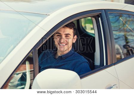 Positive Smiling Young Man Driver Sitting Behind The Steering Wheel Driving His Brand New Car. Guy P