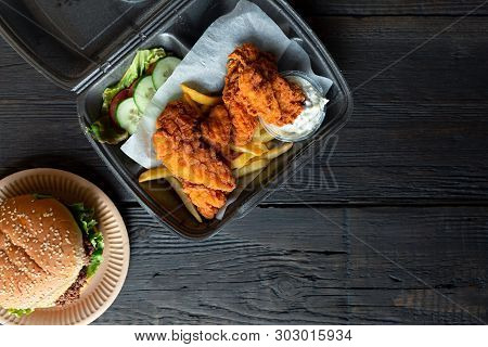 Hamburger, French Fries And Fried Chicken In Takeaway Containers On The Wooden Background. Food Deli