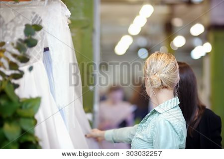 A Few Beautiful Wedding Dresses On A Hanger. Two Young Woman Is Choosing The Perfect Bridal Dress Du