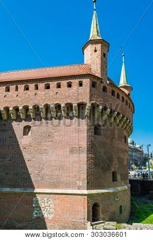 "KRAKOW, POLAND - APRIL 19, 2019: The Krakow Barbican is a barbican "" a fortified outpost once connected to the city walls. It is a historic gateway leading into the Old Town"