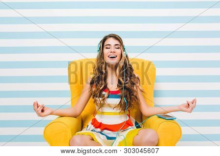 Joyful Long-haired Girl Meditating While Sitting In A Lotus Pose On Blue Striped Background. Pretty