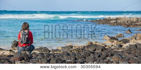 Young woman sits on the beach and looks at the sea