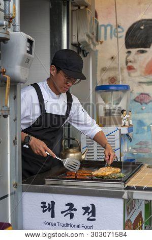 Busan, South Korea - April 2019: Young Man Vendor Cooking Buchimgae Or Korean Pancake, Korean Tradit