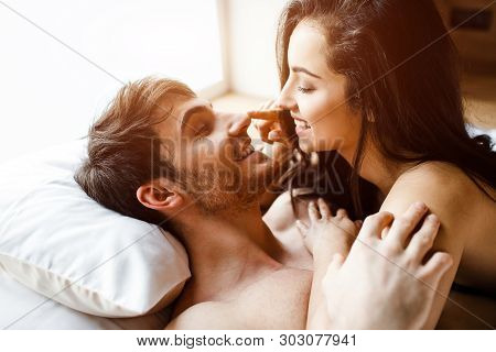 Young Sexy Couple Have Intimacy On Bed. Cheerful Nice Positive Happy People Smile To Each Other. She