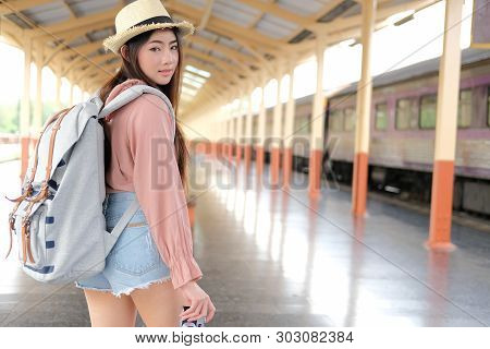 Woman  Backpacker Traveler With Camera Backpack At Train Station. Journey Trip Travel Concept