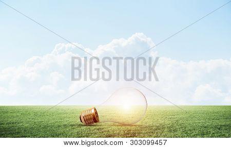 Glowing Light Bulb On Green Meadow. Electrical Light Bulb As Symbol Creative Idea Generation. Busine