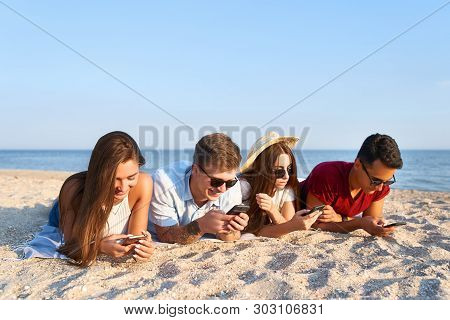 Group Of Millenials Using Smartphones Laying Together On Beach Towel Near Sea On Summer Sunset. Youn