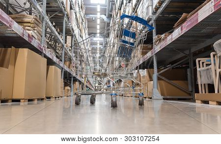 Warehouse Storage Of Retail Merchandise Shop. Trolley Shopping Cart Between Dry Grocery Shelf Sectio