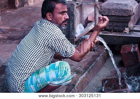Gandhinagar, Gujrat, India May 2018 - Closeup Photo Of Man Washing Hands With Water From Pipe Near S