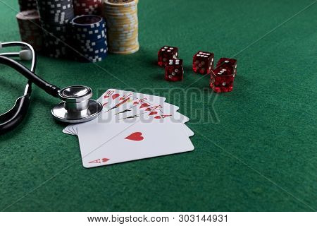 Stethoscope, red cubes and poker playing cards as a gambling with your health concept. Royal flush of hearts poster