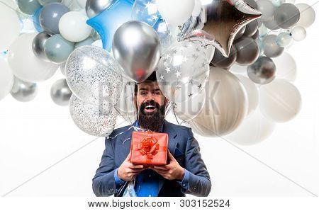 Happy Birthday Guy Holds Helium Balloons And Gift Box. Handsome Man Celebrating Something. Bearded M