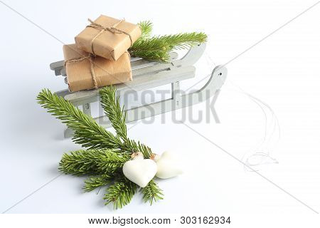 Christmas Sleigh With Gifts. New Years Concept. Decorative Toys In The Form Of Hearts And Green Bran