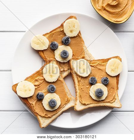 Funny Bear Face Sandwiches With Peanut Butter, Banana And Blueberries Served On Plate On Wooden Back