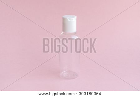 Empty jar for use on a travel on soft pink background. For all toiletries, shampoo, lotion, nail varnish remover and shower gels. Conception of care of female beauty of the face and body. A small thing which will always be located in a female handbag. poster