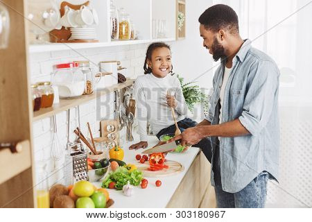 Cute Afro Kid Girl And Her Dad Cooking In Kitchen At Home. Happy Family Cooking Concept