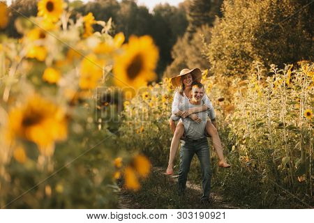Beautiful Couple In Love Is Embracing, Looking At The Sunset Over A Field Of Sunflowers. Girl In A H