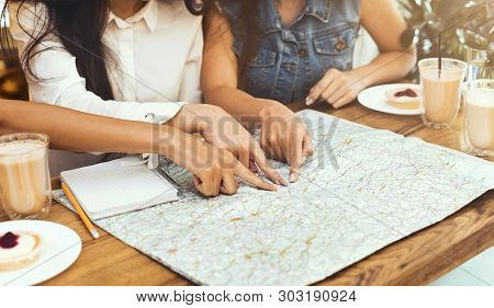 Planning Vacation With Friends. Three Women Exploring Map In Cafe, Deciding Where To Travel This Sum