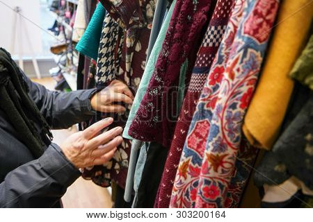 Senior Woman Going Through Clothes In Second Hand Thrift Charity Shop, Detail On Her Moving Hands.
