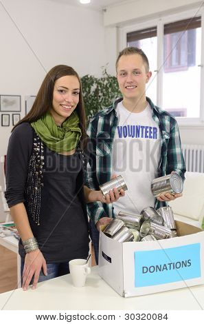 couple of young volunteers doing community service with donation box