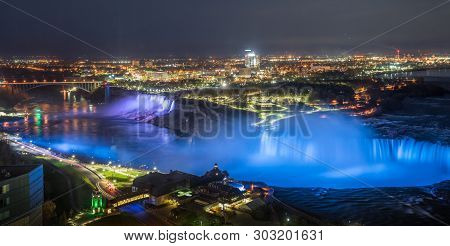 Colorfull Lights Illuminates The Water Falls On Niagara Falls In The Evening.