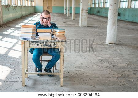 Photo Of A Student Having Difficulty While Studying For The Exam. Stack Of Books In Front Of Him On