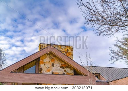 Close Up Of The Roof Of A House Against Trees And Sky With Cottony Clouds