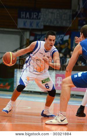 KAPOSVAR, HUNGARY – FEBRUARY 18: Kornel Kiss (with ball) in action at a Hungarian Championship basketball game with Kaposvar (white) vs. Fehervar (blue) on February 18, 2012 in Kaposvar, Hungary.