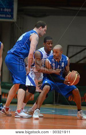 KAPOSVAR, HUNGARY – FEBRUARY 18: Kwadzo Ahelgebe (in white) in action at a Hungarian Championship basketball game with Kaposvar (white) vs. Fehervar (blue) on February 18, 2012 in Kaposvar, Hungary.
