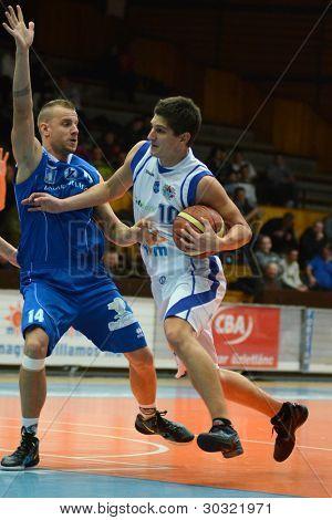 KAPOSVAR, HUNGARY – FEBRUARY 18: Gergely Kutasi (white, 10) in action at a Hungarian Championship basketball game with Kaposvar (white) vs. Fehervar (blue) on February 18, 2012 in Kaposvar, Hungary.