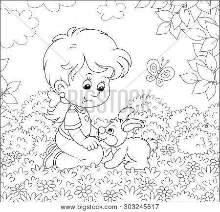 Smiling Little Girl Playing With Her Small Bunny Among Flowers On A Lawn On A Summer Day, Black And