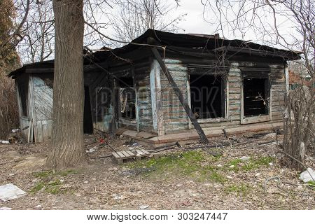 Burnt Wooden Country House. Country Residence After A Fire. Black Charred Window Walls. Misfortune,
