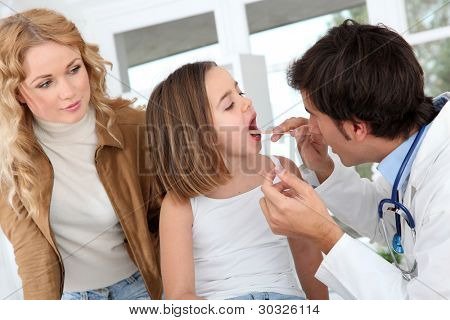Doctor looking at sick little girl throat