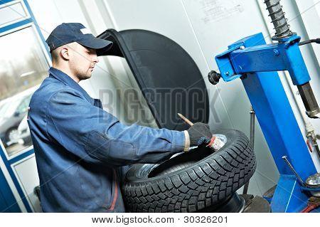 serviceman repairman worker lubricating car tyre at workshop befor fitting