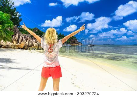 Tourist woman with raides arms enjoying at Laraie Bay with imposing shaped rock formations and turquoise Indian ocean on Curieuse Island, Seychelles. Popular tourist excursion and tropical destination poster