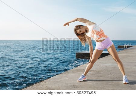 Sporty Fit Woman Focused Morning Training Session, Doing Runner Stretch Exercises, Standing Quay Nea