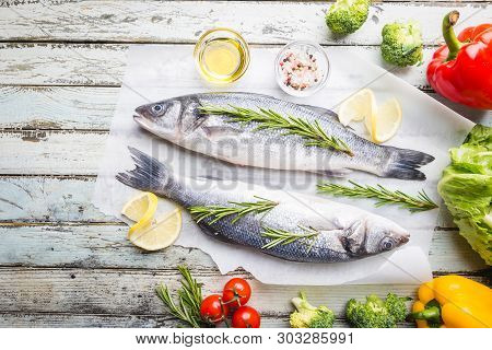 Fresh Raw Seabass And Ingredients For Cooking. Two Fish Seabass With Lemon, Spices And Herbs On Wood