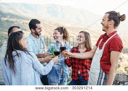Group Of Happy Friends Cheering And Toasting With Red Wine Glasses On Terrace - Young People Having