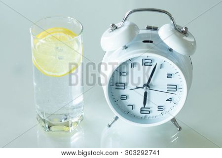 Alarm Clock And A Detox Glass Of Water With Lemon On A Glass Table. Wake Up Early In The Morning By