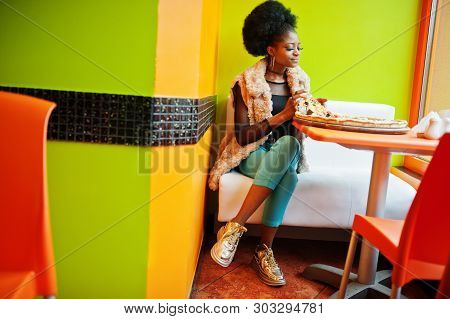 African Woman With Pizza Sitting At Bright Colored Restaurant.