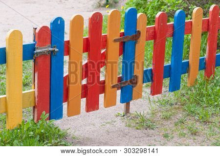 Multi-colored fence strips and wickets at the entrance to garden