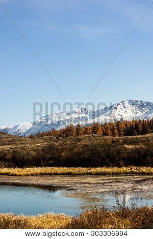 Autumn Lake With Mountain Range On Horizon. Valley With Yellow Dry Grass