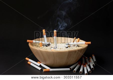 Many Cigarettes Are Placed In A Wooden Cup Of Sand On A Black Background.
