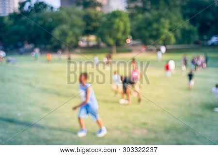 Blurry Background Children Running On Grass Lawn At The Park In America