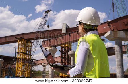 Female Foreman Working On Laptop At Bridge Construction Site. Girl Builder Controls Erection Of Car