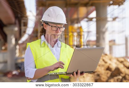 Girl foreman with laptop at construction site. female engineer works on computer under overpass under construction. poster