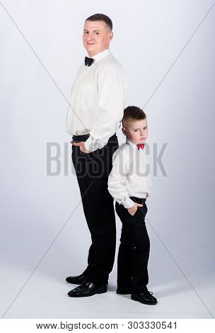 Gentleman upbringing. Little son following fathers example of noble man. Gentleman upbringing. Father and son formal clothes outfit. Grow up gentleman. Dad and boy white shirts with bow ties poster