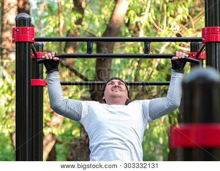 The Young Man Performs A Sports Exercise Pull-up On The Bar. Training On The Street To Develop The S