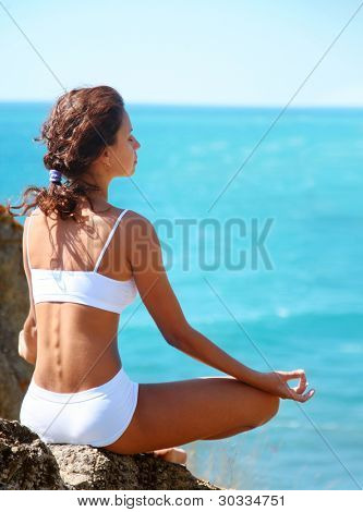 Woman meditating on a rocky seashore