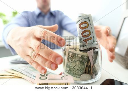 Male hands grabbing big fat jar full of US currency as greed gesture closeup poster